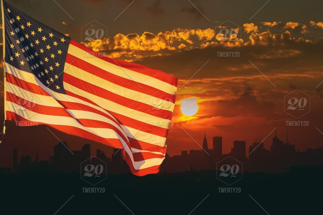 The American flag waving in sunset on the background of