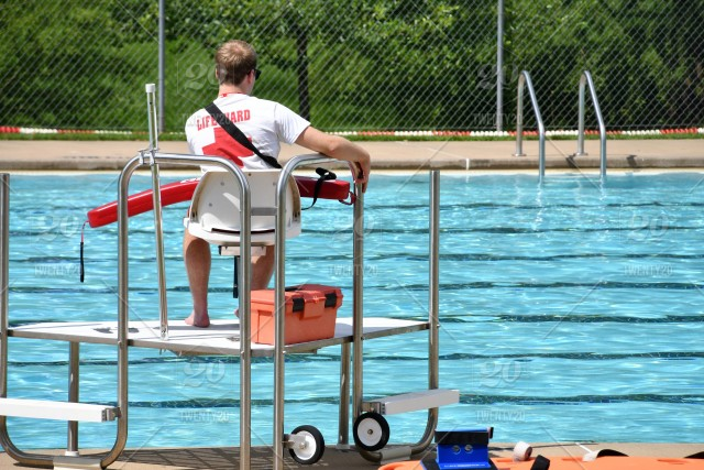 Male Lifeguard On Duty At A Public Swimming Pool