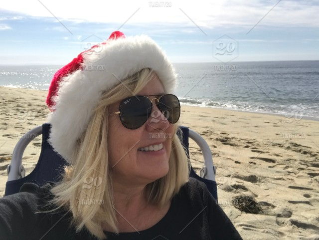 313d2cab778 A boomer woman sits on the beach with sunglasses and a santa hat ...