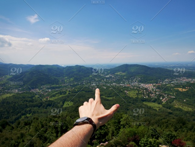 Hand pointing into the distance of a green valley in Germany (Baden
