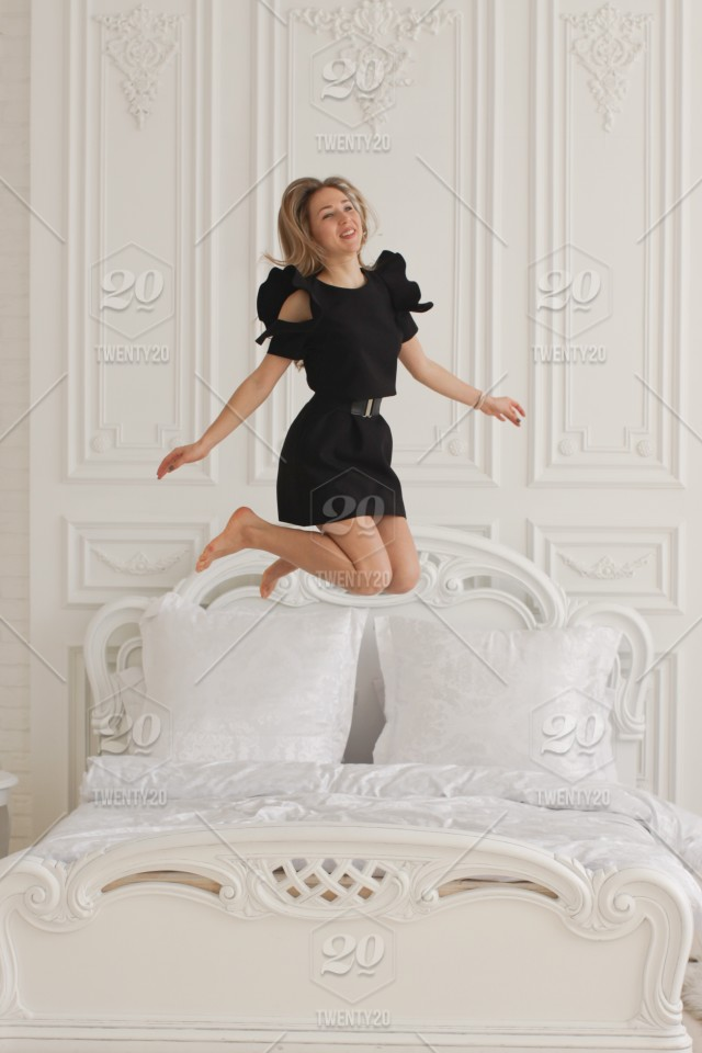 Happy young girl in black dress, bedroom with white walls ...