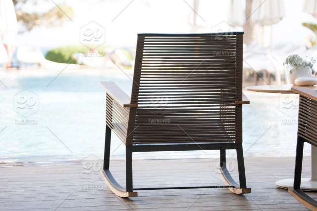 View of modern rocking chairs by the poolside on a summer holiday in
