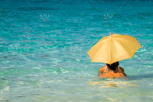 Two Beautiful Young Asian Women Standing In The Sea Under Gold