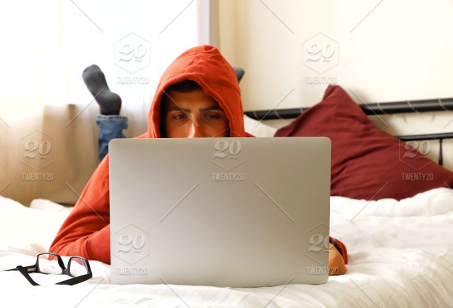 3f34f3258 A millennial guy sitting on the bed and using laptop stock photo ...