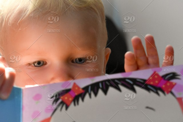 7fa3160f6f0 Little boy with blonde hair and blue eyes is reading a brightly colored ...