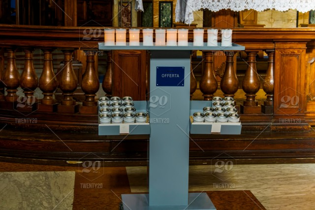 Prayer candles at a stand in a Catholic church  Lit and