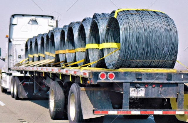 Transportation And Logistics  A Big Rig Truck Hauling Wire Coils Of Rebar On A Flat Bed Trailer