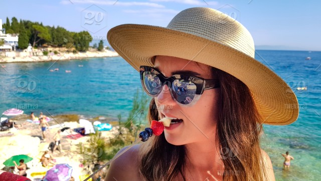 c091edbb6d Portrait of a young millenial woman with sunglasses and a hat. Girl eating  fresh fruits on a stick. Sea and beach in the background.