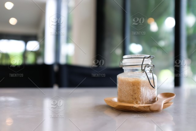 Close Up Of Small Glass Jar Of Brown Sugar On Wooden Tray With