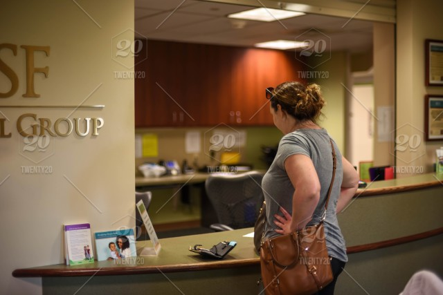 Young woman waiting to check in at doctor's office , wallet open on