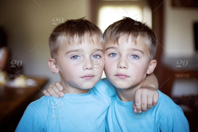 926e21985267e7 Identical twins in blue shirts with blue eyes serious look stock photo ...