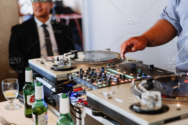 Music dj playing music on turn tables playing vinyl record for a