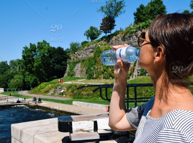 Woman traveler drinking water from a plastic bottle on a hot summer