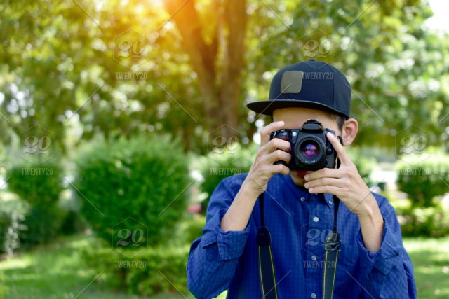 Man Holding And Using Dslr Camera And Sitting Under Tree In Public