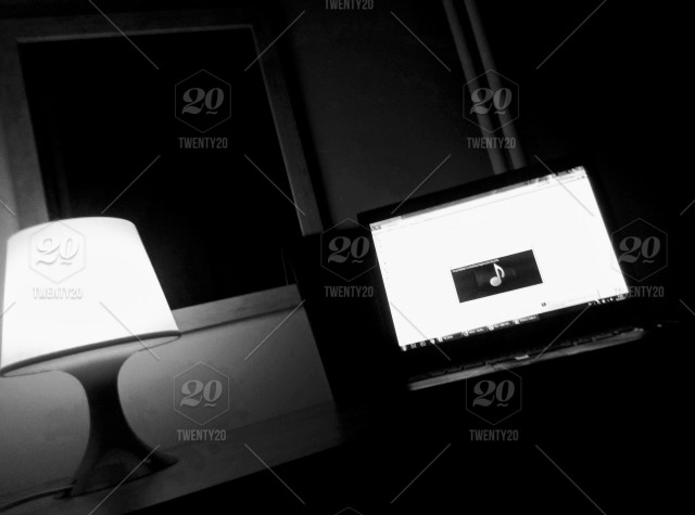 Black and white photo of a night lamp turned on with an open laptop