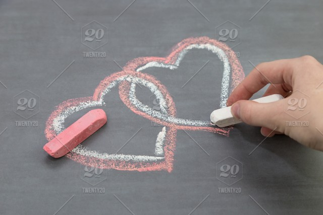 Girl Is Drawing With Chalk Two Hearts On A Blackboard Symbol
