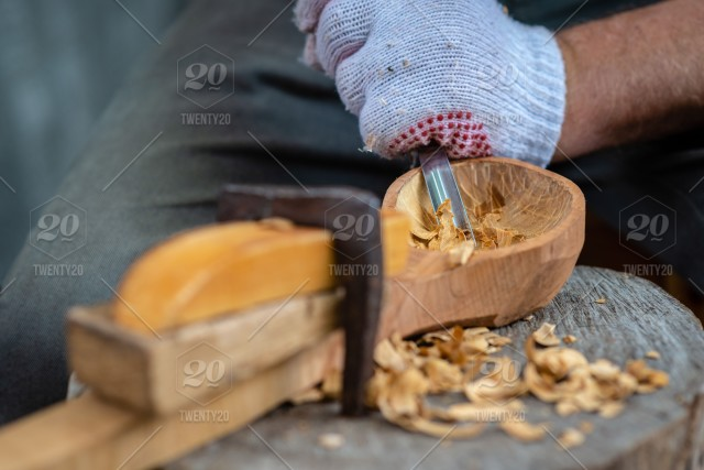 Craftsman demonstrates the process of making wooden spoons