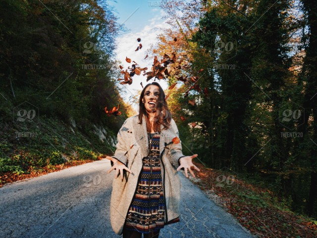 72b7839fb4 A happy and smiling young woman in casual fall clothing standing on ...