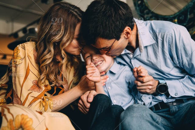 Mom And Dad Kiss Their Baby With Love Stock Photo 33357e25 2d6d 45f5 Bf0f D6994b718328