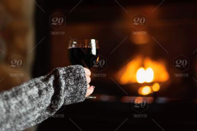 Enjoying a glass of wine by a cozy fire in luxury cabin room at