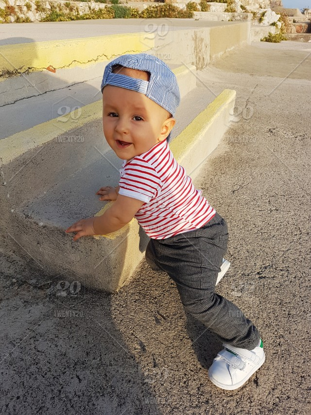 5a390c2409b Cute Baby Boy 1 Year Wearing A Cap Backwards And Striped Clothes ...
