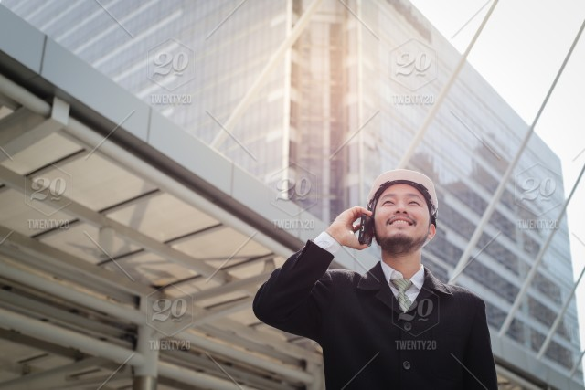 Young asian engineer man talking on mobile phone in modern