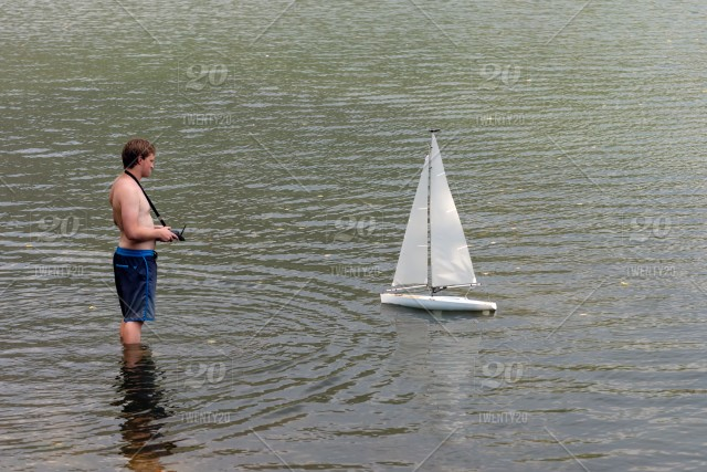 A man remotely controls a sailing yacht scale model in a