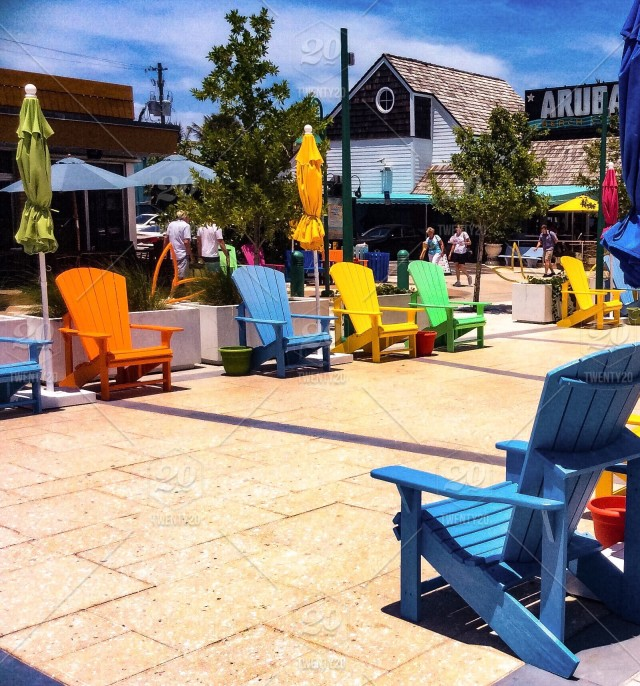 Colorful Adirondack chairs and umbrellas line the plaza ...