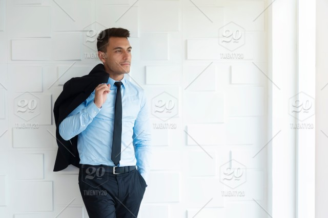 df577108e6c0 Portrait of smart business man in suit standing at white wall in ...