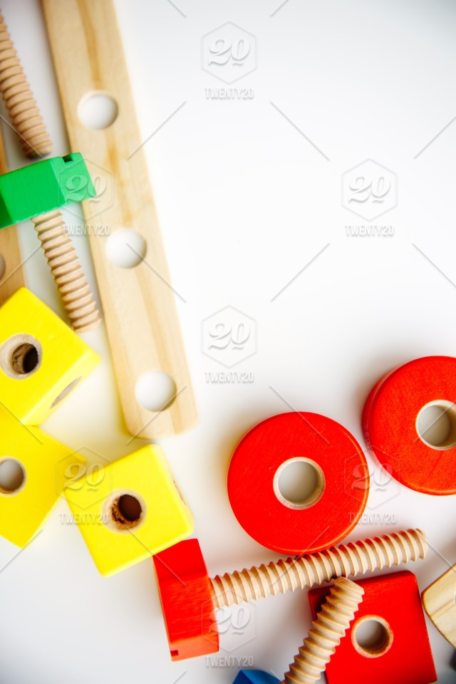 Closeup of toy wooden bricks and sticks on white table background
