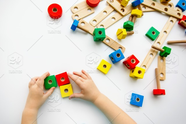 Close up of child hands playing with colorful wooden bricks
