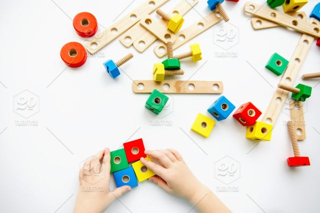 Close up of child hands playing with colorful wooden bricks at the