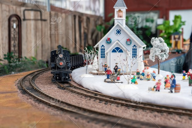 Model train set, black steam engine with white church and