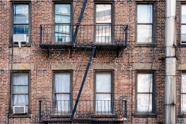 Old brick building with balconies and fire escape in ...