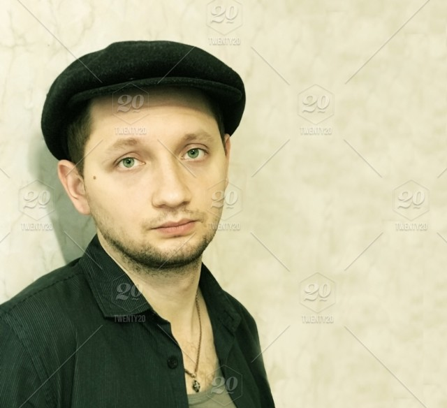 7e3bb60a7a8 Young man in the flat cap stock photo 797a3305-7ce1-4cb5-9d15 ...