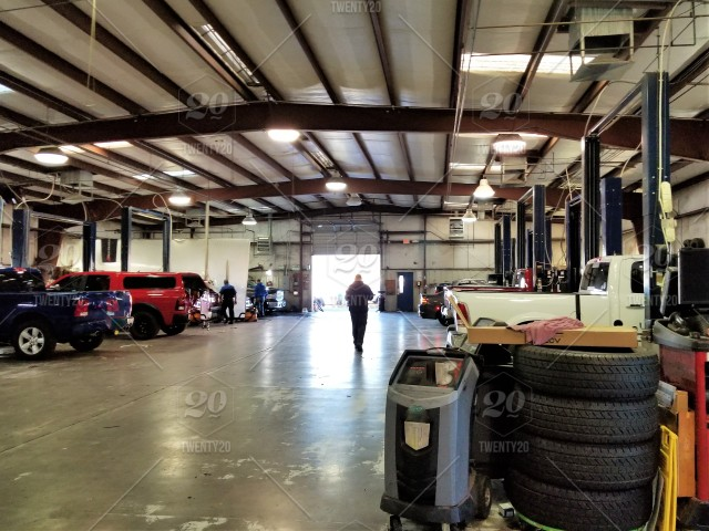 Automotive Repair! Inside the automotive repair area of a large car  dealership. Pick up trucks in various stages of repair or maintenance, as  the garage mechanics work on the vehicles as the