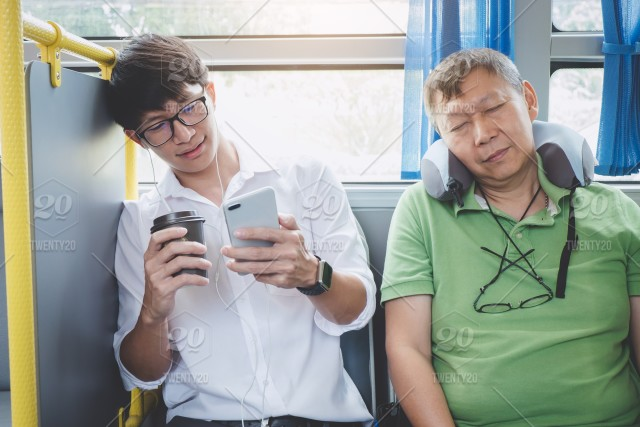 Young Asian man traveler sitting on a bus using smartphone for