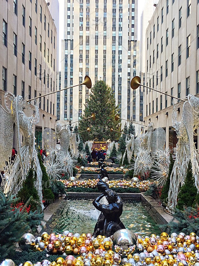 Christmastime in New York City! Festive christmas ornaments beautifully surround Rockefeller Center as the majestic Christmas tree stands tall in the ...