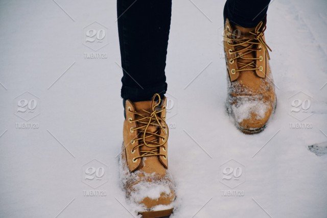 e630b4c000a Feet of a teenage girl in winter yellow boots walking in a snow stock ...