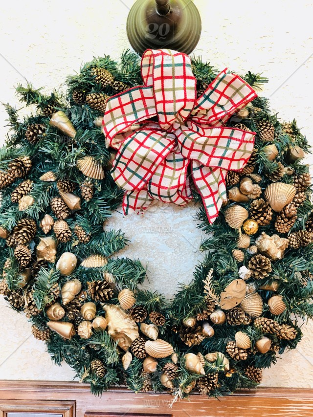 Gold, Christmas wreath decorated with golden seashells and pine cones, coming together with a bow on top.