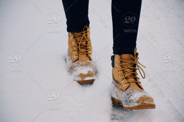 1507641acdb Feet of a teenage girl in yellow winter boots walking in a snow ...