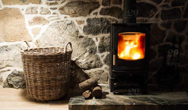 A wood burning stove and logs burning brightly in an old stone cottage