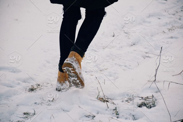 58b78ac4e2a Feet of a teenage girl in yellow winter boots walking away in a snow ...
