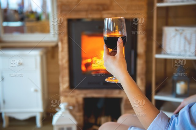 Woman resting with glass of red wine near fireplace,image