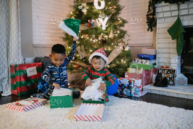 Christmas Gifts For Brother.Two Diverse Little Brothers Opening Gifts Presents Next To