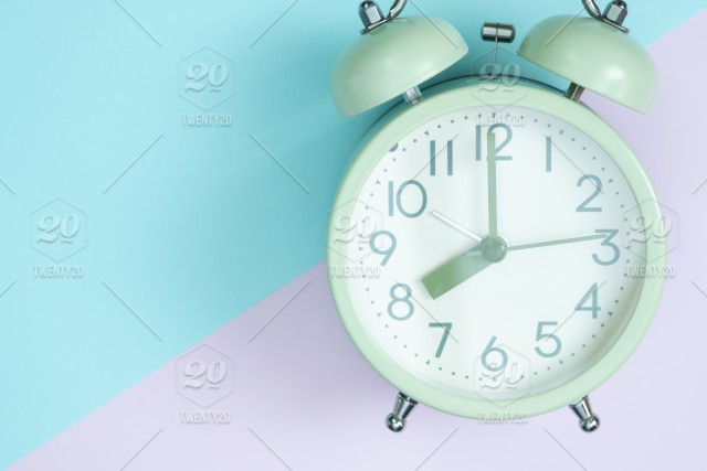 Flat lay vintage alarm clock on sweet pastel colour paper