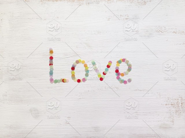 """b8b5f1662c70 """"Love"""" on white wooden texture background. Pretty pastel colours."""