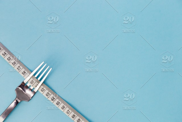 Metal Dining Fork And Centimeter Tape On Color Background Symbolizes Weight Loss Free Space For Text No People No Person Nobody Weight Healthy Fat Food Overeating Health Lifestyle Background Nutrition Dieting Concept