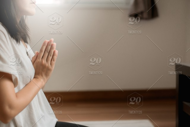 Asian female with hand in praying buddha statue position