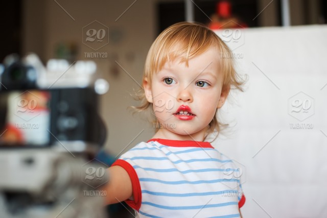 Little Funny Blond Baby Girl Make Up Lips With Mom S Red